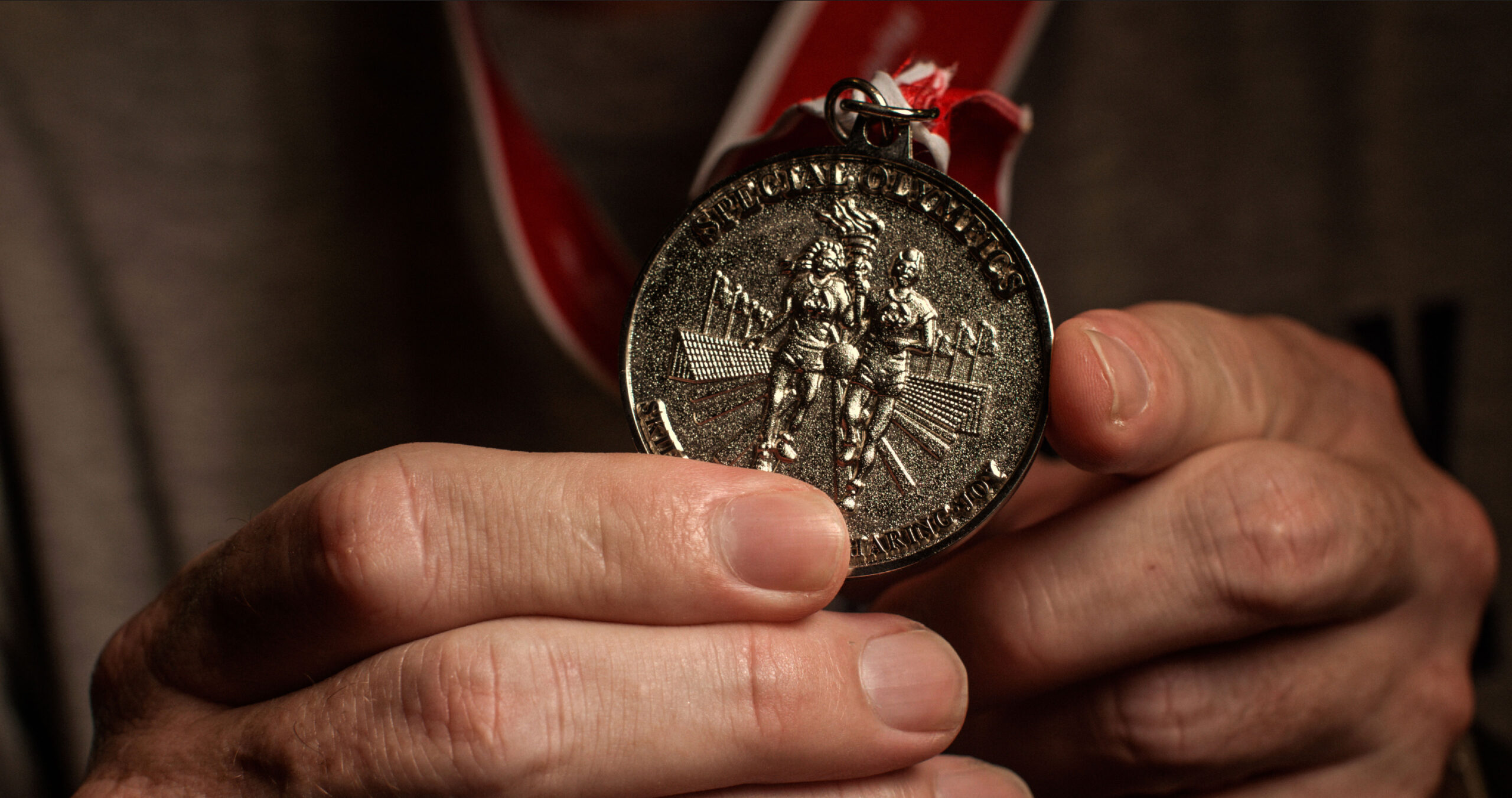 man holding a special olympics medal